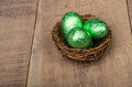 Small bird's nest with green foil eggs Stock Photography