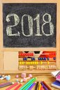 Small blackboard in wooden abacus frame and hand written 2018 new year greeting on it. Scattered stationery, colorful pencils, ch Royalty Free Stock Photo