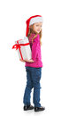 Small blond girl hiding big present behind back looking at camera over shoulder smiling isolated on white background Stock Images