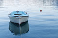 Small blue fishing boat in calm water Royalty Free Stock Photo