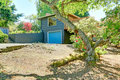 Small blue house with garage and large front yard with trees spring Stock Images