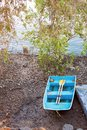 Small Blue Rowboat With Yellow Oars On Muddy River Bank Royalty Free Stock Photo