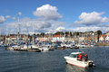 Small boat entering anstruther harbour fife white motor with lots of other yachts and boats at their moorings in front of the Royalty Free Stock Photography