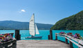 Small boat  sailing past a wooden dock on Lac d& x27;Annecy, France. Royalty Free Stock Photo