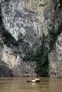 Small boat under massive limestone cliff Stock Photos