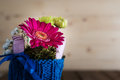Small bouquet in knitted vase closeup on with gerbera and chrysanthemum blue on countrified wooden table Stock Images