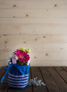 Small bouquet in knitted vase with gerbera and chrysanthemum blue on countrified wooden table Stock Images