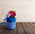 Small bouquet in knitted vase with gerbera and chrysanthemum blue on countrified wooden table Stock Image
