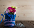 Small bouquet in knitted vase with gerbera and chrysanthemum blue on countrified wooden table Royalty Free Stock Image