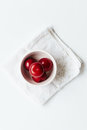 Small bowl of red plums on white vintage napkin Royalty Free Stock Photo
