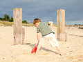 Small boy on a beach digging with toy spade sandy Royalty Free Stock Image