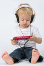 A small boy in blue jeans with headphones playing the game device Royalty Free Stock Photos