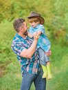 Small boy child help father in farming. father and son in cowboy hat on ranch. kid in rubber boots. happy man dad in Royalty Free Stock Photo