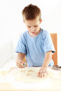 Small boy cutting cookies Royalty Free Stock Photos