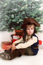 The small boy in dress of filibuster sits against xmas presents Royalty Free Stock Photography