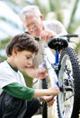 Small boy fixing his bicycle tyre with grandfather Stock Photography