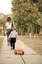 Small boy following Mum with a truck Stock Photo
