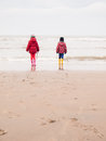 Small boy and girl on the beach in winter clothing rubber boots a winter looking out to sea Stock Images