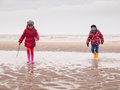 Small boy and girl paddling on the beach in winter clothing rubber boots spalshing in a tidal pool a winter Stock Images