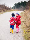 Small boy and girl walking hand in hand winter clothing along a path througha wooded landscape Stock Photo