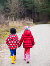 Small boy and girl walking hand in hand winter clothing holding hands along a path througha wooded landscape Royalty Free Stock Image