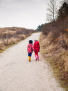Small boy and girl walking hand in hand winter clothing holding hands along a path through a wooded landscape Royalty Free Stock Photography