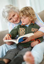 Small boy and happy grandmother reading book Royalty Free Stock Image