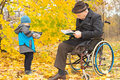 Small boy with his handicapped grandfather outdoors in a colourful fall garden the old men sitting in wheelchair reading Royalty Free Stock Photo