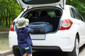 Small boy loading his suitcase into the open back of a hatchback car as he prepares to leave on holiday Royalty Free Stock Photos