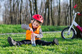 Small boy opening a bottle of water dressed in safety helmet and jacket while sitting on green grass in wooded park with his Royalty Free Stock Photography