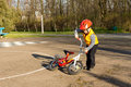 Small boy picking up his bicycle dressed ready to go out for a ride in colourful safety gear and a red helmet on a quiet country Royalty Free Stock Photo