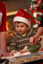 Small boy in santa claus hat at christmas baking helping watching mother and grandmother making cake Stock Photo