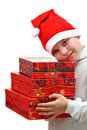 Small boy in Santa red hat carrying three presents Stock Photos