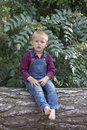 stock image of  Small boy sitting on the old tree trunk in the park