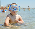 Small boy sitting shallow water near seashore wearing goggles holidaymakers enjoying themselves seaside visible distance Royalty Free Stock Photography