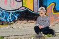 Small boy sitting thinking alone in sunshine on sidewalk in front of a wall covered in colourful graffiti or sulking staring down Royalty Free Stock Photography