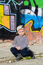 Small boy sitting thinking cute on pavement in front of colourful wall covered in painted graffiti with his baseball cap pulled Royalty Free Stock Image
