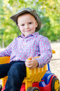 Small boy sitting on a toy truck Royalty Free Stock Photo