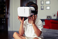 Small boy on sofa watching something in virtual reality glasses