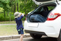 Small boy struggling to load his suitcase into the open back of a hatchback car as he prepares leave on summer holiday Royalty Free Stock Images