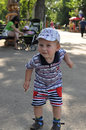 Small boy by summer in park stands and smiles Royalty Free Stock Image