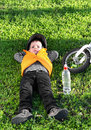 Small boy taking a rest on the grass as he relaxes alongside his bicycle after stopping for refreshing drink of bottled water Royalty Free Stock Photos