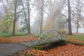 Small bridge over dry creek in park with fog Royalty Free Stock Photo