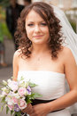 Small brunette bride with veil holding bridal bouquet closeup portrait of Stock Photos