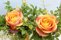 Small bunch with two orange roses and fine leaved blueberry bran Royalty Free Stock Photo