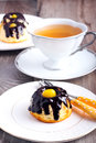 Small bundt cake with chocolate glaze and candied lemon and cup of tea Royalty Free Stock Photo