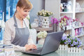 Small business entrepreneur florist in her store flower action managing working by laptop Royalty Free Stock Photo
