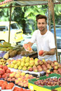 Small business owner selling organic fruits at an open street market and vegetables to a woman carrying a shopping paper bag with Royalty Free Stock Image