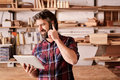 Small business owner in workshop with phone and digital tablet smiling bearded man of a woodwork standing his studio talking on Royalty Free Stock Photo