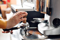 Small business, people and service concept - woman or waiter in apron with holder and tamper preparing coffee at coffee